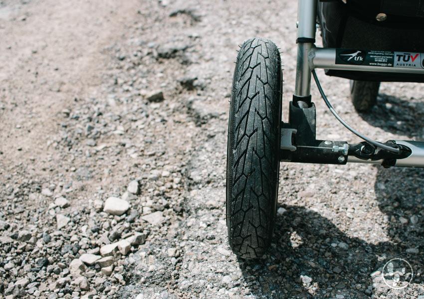 Kinderwagenrad auf bröckeligem Asphalt