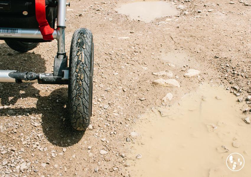 Kinderwagenrad auf Weg mit Pfützen